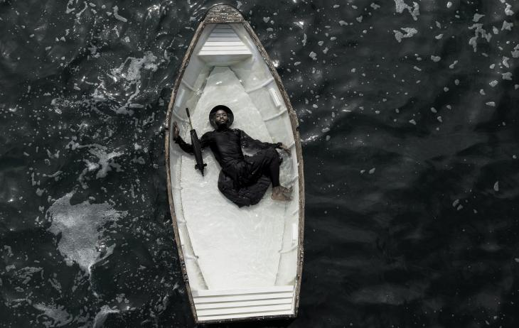 A man dressed in black lies in a white boat that is partially filled with water