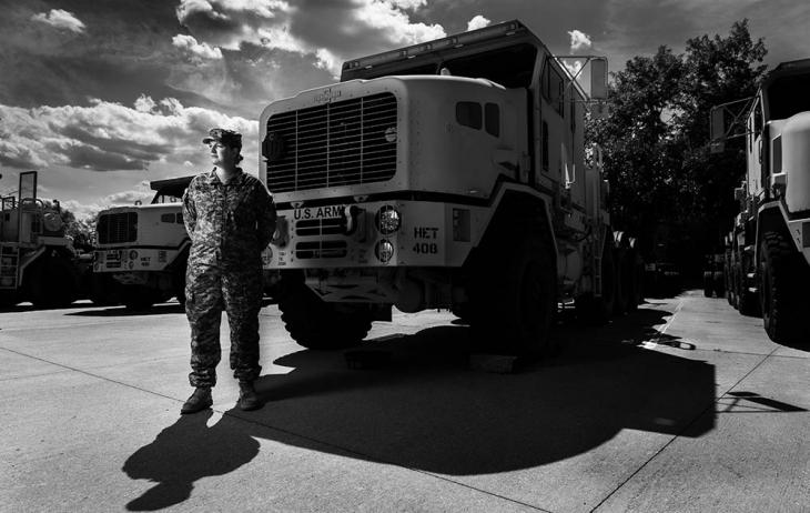 A woman stands in a camouflage military uniform in front of a large truck
