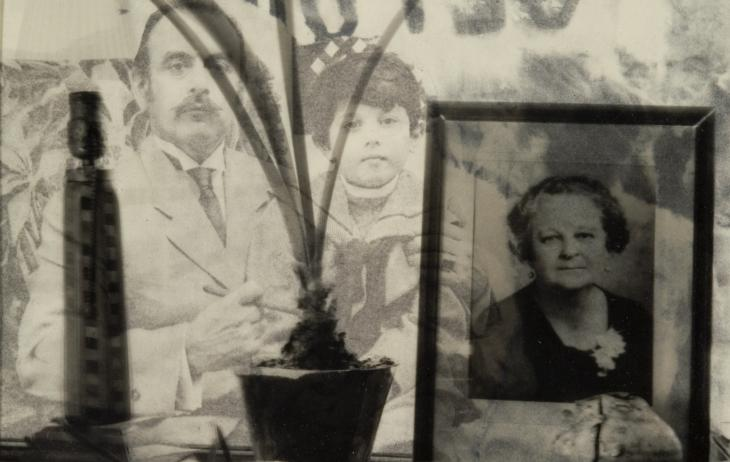 Transparency over xerox. Background is of a man holding a young boy who is wearing a sailor shirt. There is a photograph of an elderly woman in the right foreground, a potted plant in the center foreground, and a lamp in the left foreground.