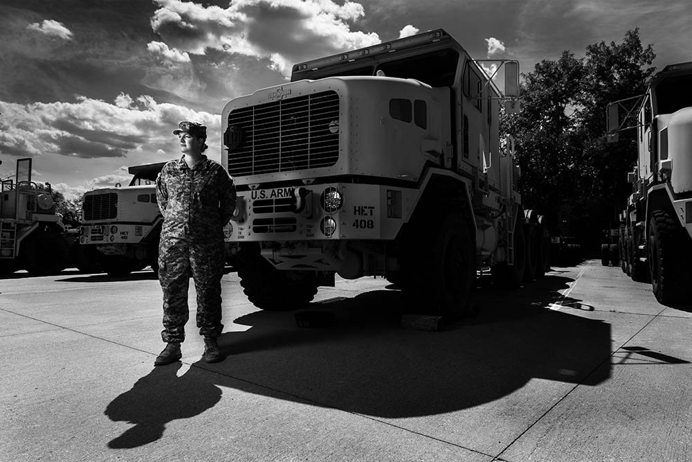 Black and white photograph of Sgt. Tara Arteaga standing in uniform in front of a truck