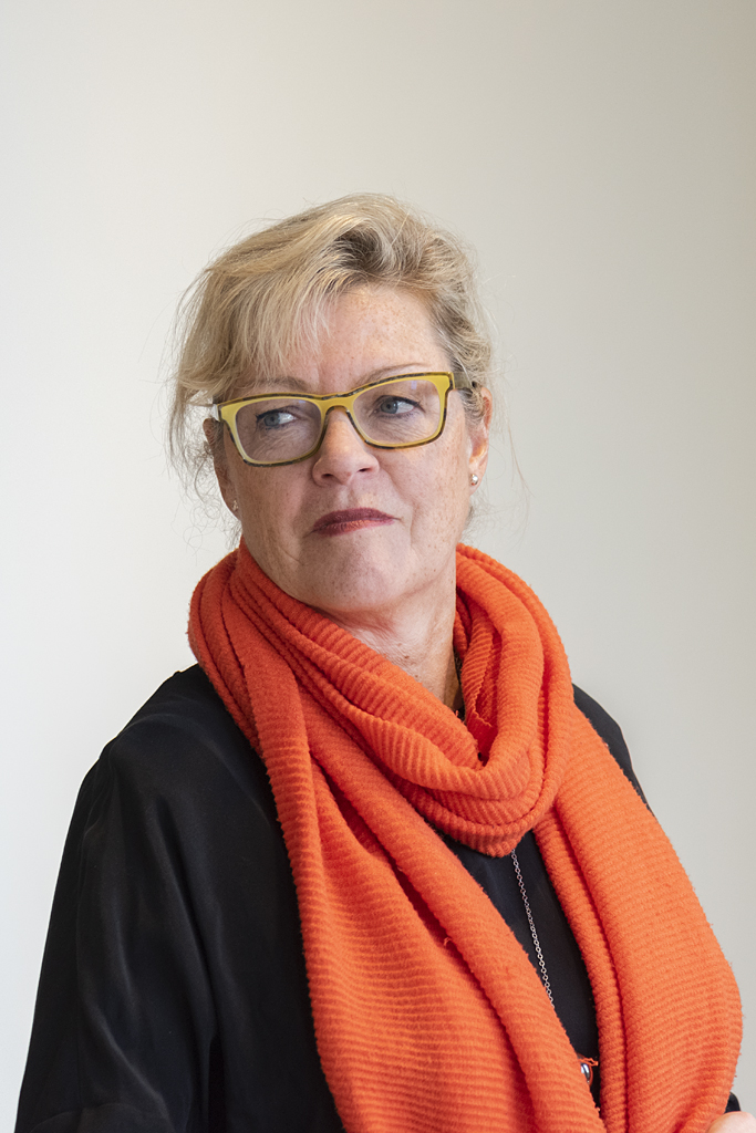 Photographic color portrait of a light-skinned woman with blonde hair, yellow glasses, and a bright orange scarf