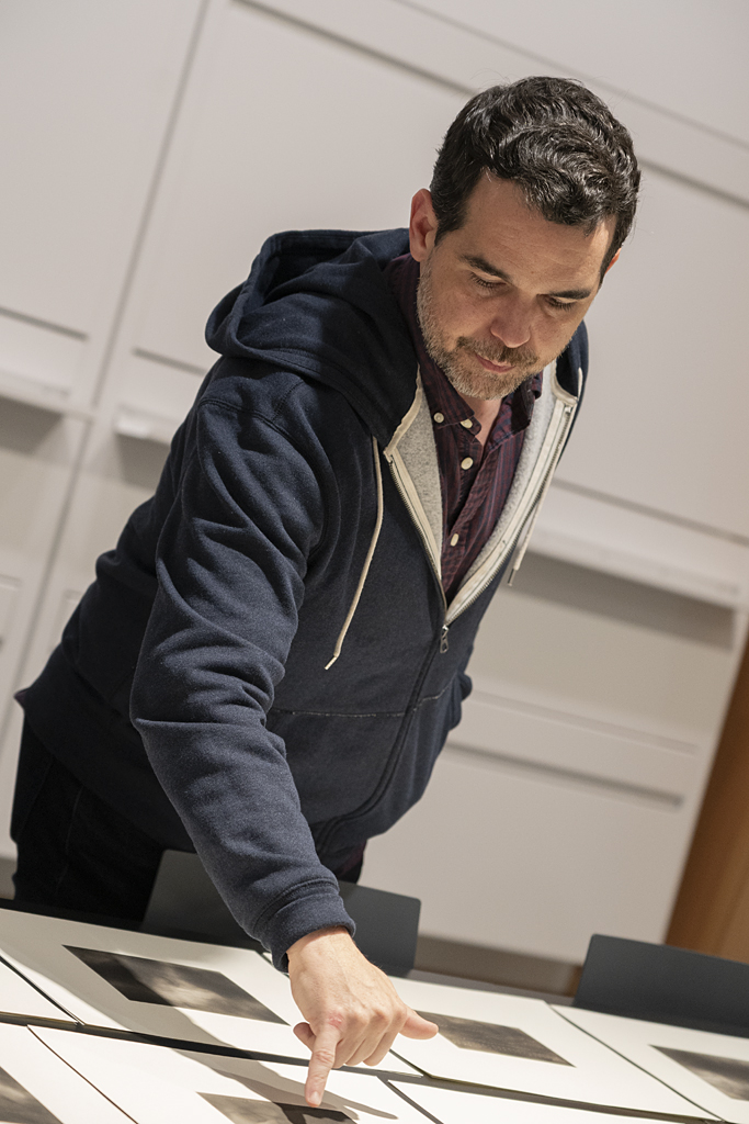 Photograph of Dario Robleto, a dark haired man in a hoodie, looking at prints on a table