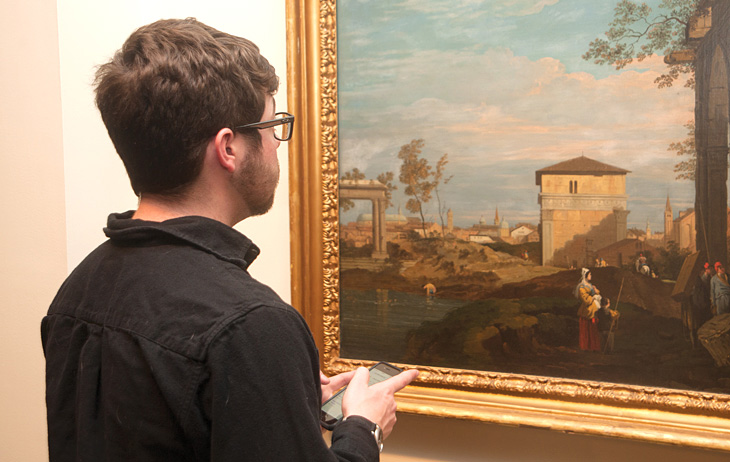 Man in front of painting holding a mobile phone