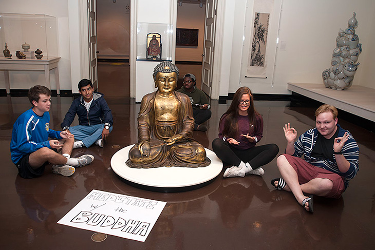 Children around Buddha statue meditating with sign that reads Meditate with the Buddha