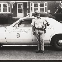 <a href='http://collection.spencerart.ku.edu/eMuseumPlus?service=ExternalInterface&module=collection&objectId=54772&viewType=detailView' target='_blank'><i>untitled (police officer with squad car)</i> by Thaddeus Holownia</a>