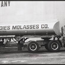 <a href='http://collection.spencerart.ku.edu/eMuseumPlus?service=ExternalInterface&module=collection&objectId=54830&viewType=detailView' target='_blank'><i>untitled (trucker posing with molasses tanker truck)</i> by Thaddeus Holownia</a>