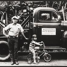 <a href='http://collection.spencerart.ku.edu/eMuseumPlus?service=ExternalInterface&module=collection&objectId=54841&viewType=detailView' target='_blank'><i>untitled (man and child in front of a tow truck)</i> by Thaddeus Holownia</a>