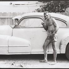 <a href='http://collection.spencerart.ku.edu/eMuseumPlus?service=ExternalInterface&module=collection&objectId=54872&viewType=detailView' target='_blank'><i>untitled (a man smoking posed with a car)</i> by Thaddeus Holownia</a>