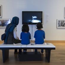 "Visitors watch a video in the exhibition ""Temporal Turn: Art and Speculation in Contemporary Asia""."