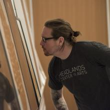 A student inspects a work of art in the Stephen H. Goddard Study Center.