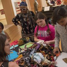 Artist Faith Ringgold works with students during a quilt workshop.