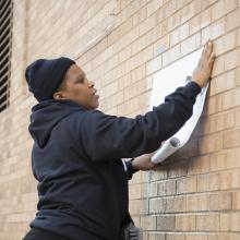 Bell begins to unroll and affix her artwork <i>Charlottesville</i> to the west wall of Chalmers Hall. This large-scale installation is part of Bell's <i>Counternarratives</i> series that questions and revises racial bias in media.
