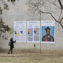 A student takes a picture of Bell's <i>A Teenager with Promise, Annotated</i> installation on the side of Watson Library. This artwork is part of Bell's <i>Counternarratives</i> series.