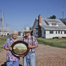 <a href='http://collection.spencerart.ku.edu/eMuseumPlus?service=ExternalInterface&module=collection&objectId=58321&viewType=detailView' target='_blank'><i>Laurence and Pauline Schwarm in front of their 100-year old farm, Greensburg, Kansas, June 2011,</i> by Larry Schwarm,</a>