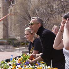 Artist Paul Hartfleet and Spencer Museum interns give pansies away to passersby in from of the Kansas Memorial Union