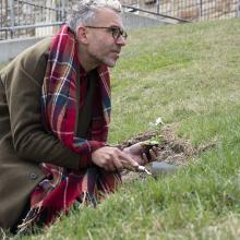 Artist Paul Hartfleet plants a pansy by the Campanile on KU's campus to mark an incident of homophobic abuse