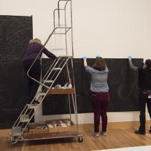 Artist Sandy Winters, Assistant Collections Manager Sarah Schroeder, and Head of Collections Sofia Galarza Liu begin to affix a portion of <i>Long Night's Journey into Day</i> in the Perkins Central Court
