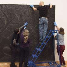 Head of Collections Sofia Galarza Liu, artist Sandy Winters, Exhibition Designer Richard Klocke, and assistant collections manager Sarah Schroeder affix a portion of <i>Long Night's Journey into Day</i> in the Perkins Central Court