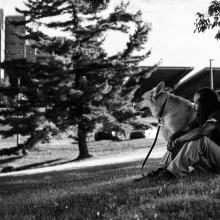 Army veteran Aquil Thomas with his dog on the grass outside of a VA medical center. Photographed by Steve Gibson