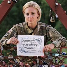 "Major Kristen Hesterberg is pictured here with the Old Red Bridge ""Love Locks,"" which is a place where she finds peace. Photographed by Chuong Doan"
