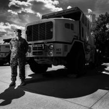 Sergeant Tara Fajardo Arteaga, who has served in the Army National Guard since 2008, stands in uniform in front of a truck. Photographed by Steve Gibson